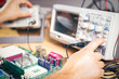 Engineer tests electronic components with oscilloscope in the service center