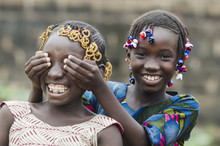 African Girls Playing Peekaboo Outdoors Laughing And Smiling Together (Happiness Symbol)