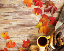 Cup Of Tea With Plaid And Leaves On The Wood Background.
