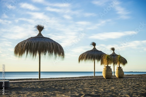 Low Angle View Of Thatched Roof Umbrella On Beach Against Sky