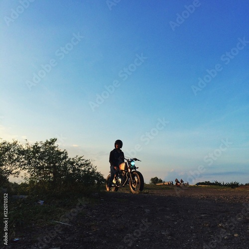 Man Sitting On Motorcycle At Field Against Blue Sky