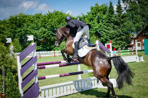 Fotobehang Paardrijden Reitturnier - Pferd und Reiter beim Absprung über ein Hinderniss