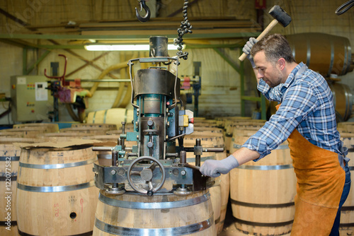 cooper at work hammering top on to wooden barrel