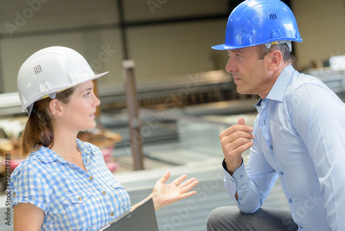 Photo Man and woman in workplace wearing hardhats
