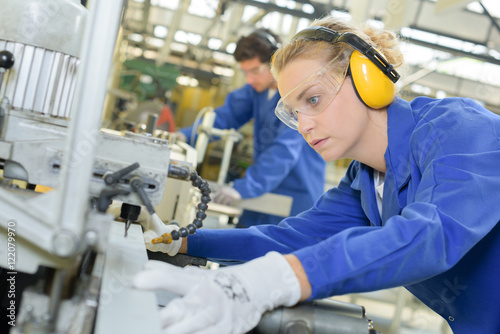 Foto Woman using industrial machine