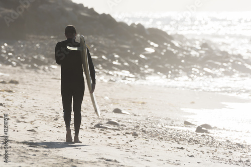 Male surfer walks the beach at sunrise in Long Island, New York Plakát