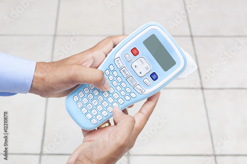 man using handheld label maker machine buy this stock photo and