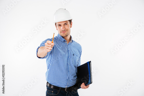 Happy young man architect in hard hat pointing on you