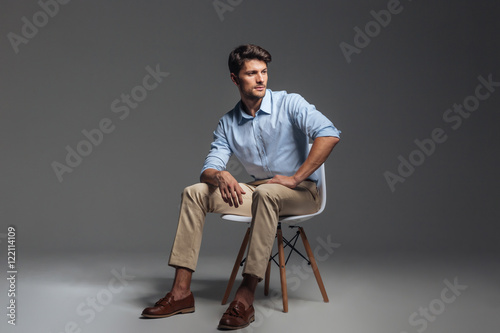 Fototapeta Pensive brunette man in blue shirt sitting on the chair obraz