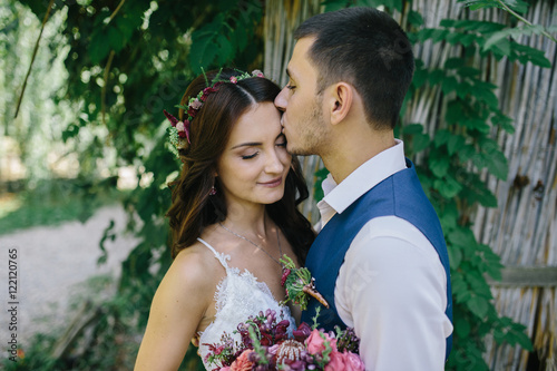 Fotografie, Obraz  happy groom in a dark blue suit kisses a beautiful bride in a white wedding dres