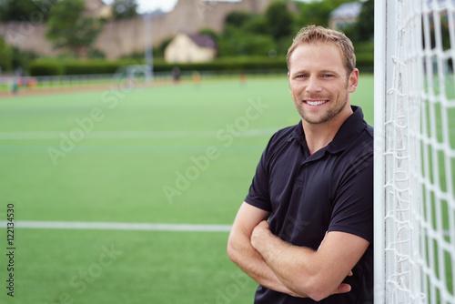 mann lehnt lächelnd an einem fußballtor auf dem sportplatz