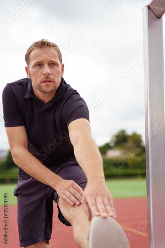 Photo  sportler dehnt seine wade vor dem training