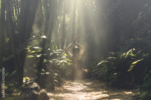Poster Bamboe woman meditating in a bamboo forest