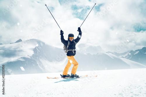 Fotografía Glücklicher Skifahrer streckt die Skistöcke in die Luft