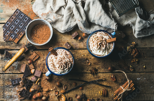 Poster Chocolade Hot chocolate with whipped cream, nuts and cinnamon in enamel mugs with ingredients around on rustic wooden background, top view, horizontal composition