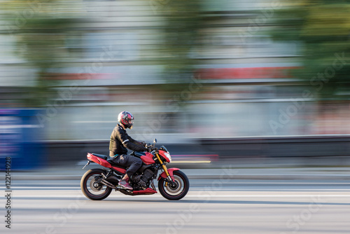 фотография  Motorcycle rider in the city traffic in motion blur