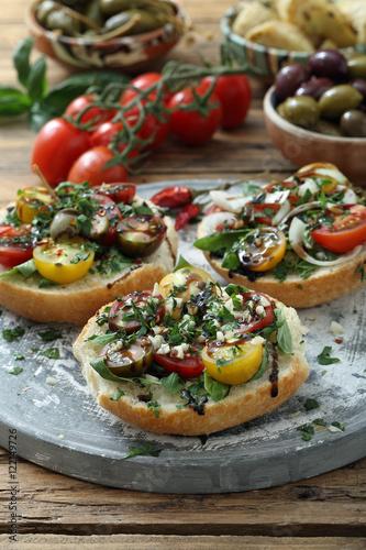 Fotografie, Obraz  panini con pomodoro e erbe varie su sfondo tavolo di legno rustico