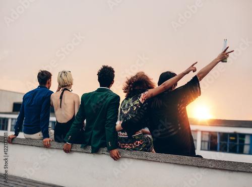 Friends enjoying drinks on rooftop at sunset Fototapeta