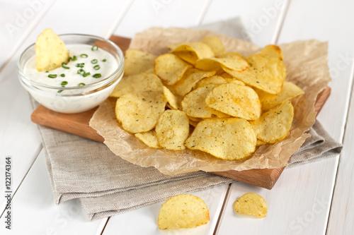 Fotografie, Obraz  Potato chips on a parchment on a table.