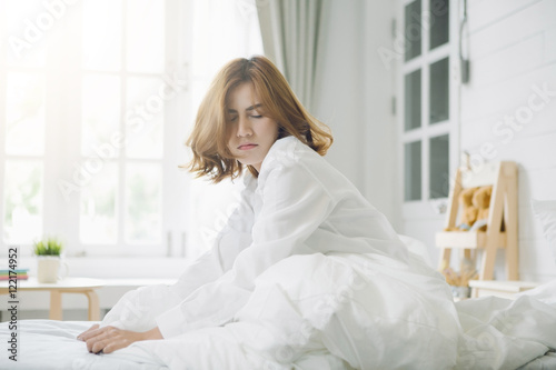 Fotografering  Woman lethargic in bed after wake up,flare light