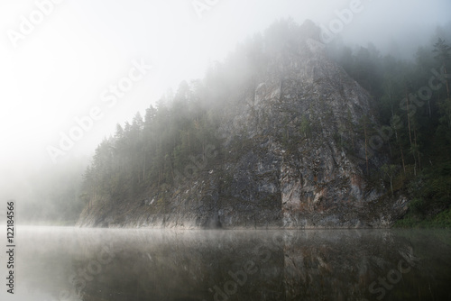Fototapeten Wald Rocky mountain in the morning fog with reflection in the river
