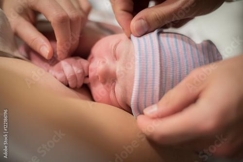 Photo  New born boy on mom's chest. Dad adjusting hat.
