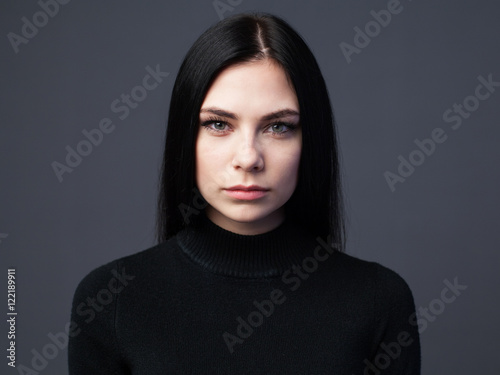 Fotografiet  Beautiful serious woman with sad look, gray background