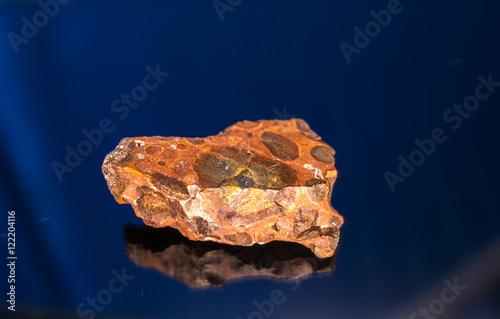 Photo Radial blurred background view of bauxite mineral under sun light on black backg