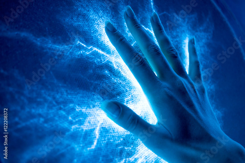 Obraz The touch of the hand to the luminous electric surface-emitting - fototapety do salonu