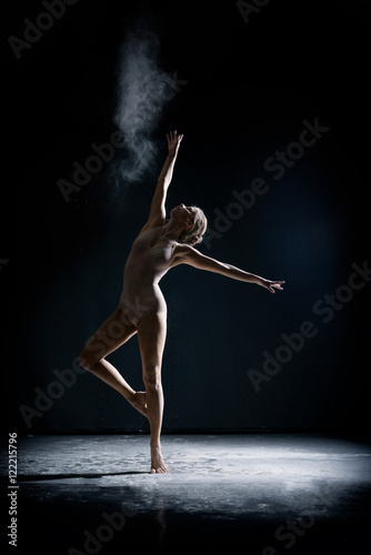 Vászonkép Image of artistic girl dancing with dust in studio