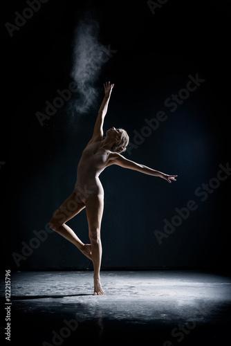 Slika na platnu Image of artistic girl dancing with dust in studio