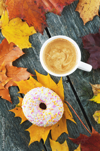 Doughnut and coffee with milk on a wooden background and maple leaves