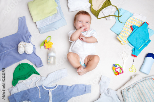 Baby on white background with clothing, toiletries, toys and health care accessories Canvas Print
