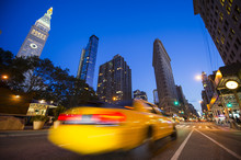 Defocus Motion Blur View Of Yellow Taxis Driving Through The City Streets At Dusk In New York City, USA