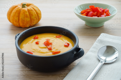 Fotografie, Obraz  Pumpkin soup with chopped red peppers in a brown ceramic bowl with handles, a  munchkin pumpkin, a bowl with red chopped peppers, a grey napkin and a soup spoon on light brown wooden background