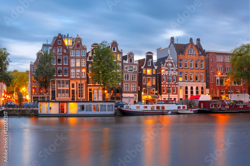 Ingelijste posters Amsterdam Amsterdam canal Amstel with typical dutch houses and boats during twilight blue hour, Holland, Netherlands.