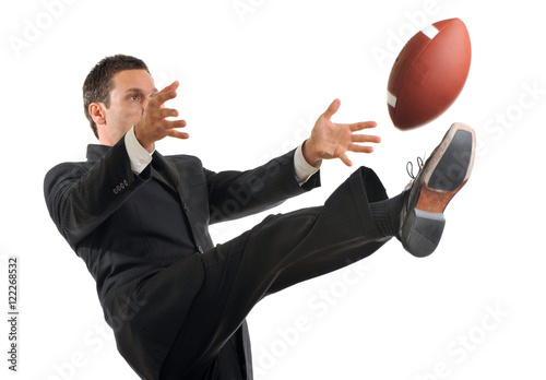 Fotografija Businessman Kicking American Football on White