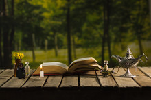 Thick Book Lying Open On Wooden Surface, Small Brown Bottle With Flowers, Aladin Style Lamps And Wax Candle Next To It, Magic Concept Shoot