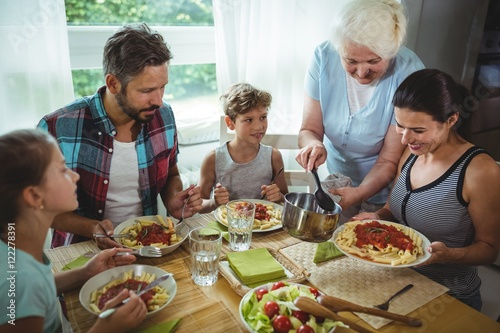 Fototapeta Elderly woman  serving meal to her family obraz