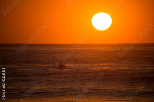 Silhouette man swimming in sea against sunset