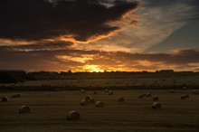 Dramatic Sunset With Dark Clouds Over A Field With Hay Bales, Whitburn, Tyne And Wear, England