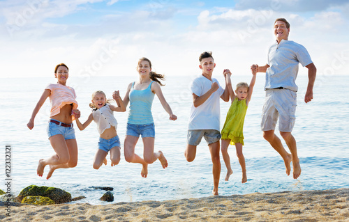 Fotografie, Obraz  Large family jumping up together on beach on clear summer day