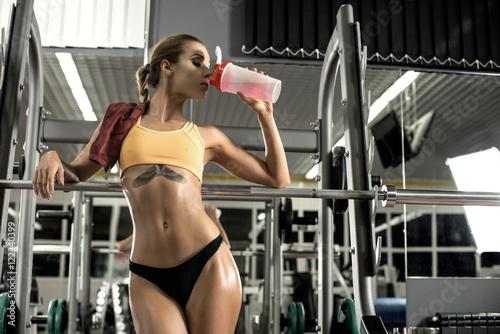 Fotografia  fitness woman tired in gym drink sportive nutrition of shaker