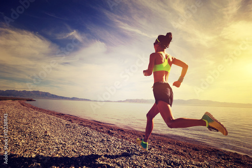 Fotografia  healthy young fitness woman trail runner running on sunrise seaside