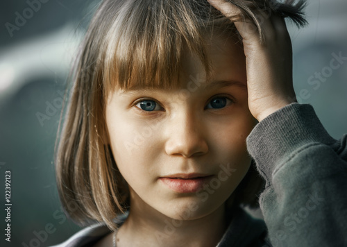 Sad Teenager Girl With Short Blonde Hair And Blue Eyes On Gray
