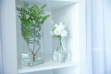 Beautiful flowers in glass vases on white shelf
