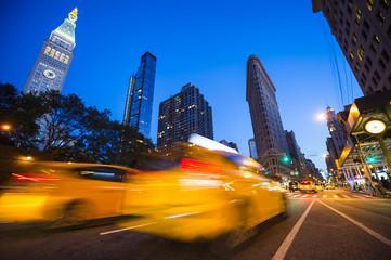 Defocus motion blur widok żółtych taksówek jazdy ulicami miasta o zmierzchu w Nowym Jorku, USA