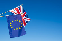 European Union And British Union Jack Flag Flying In Front Of Bright Blue Sky In Preparation For The Brexit EU Referendum