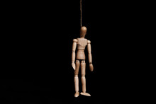 Low Key, Wooden Marionette Puppet Hangman By Rope, On Black Background
