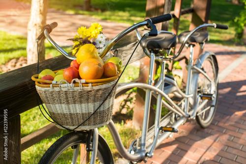 Zdjęcie XXL Kosz owoców na rowerze. Rower i bukiet na ogrodzeniu. Zorganizuj piknik dla dwojga. Ciepłe dni w sierpniu.